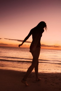 Silhouetted woman walking at the beach at sunset