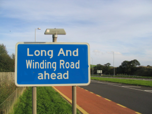 long_and_winding_road_ahead_sign_by_pudgemountain-d5uqpux